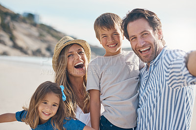Buy stock photo Cropped portrait of an affectionate couple carrying their two children and posing for a selfie on the beach