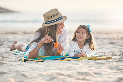 Buy stock photo Full length shot of a playful young mother lying on the beach and blowing bubbles with her daughter