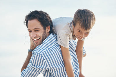 Buy stock photo Cropped shot of a handsome mature father bonding with his son and carrying him on his shoulders on the beach