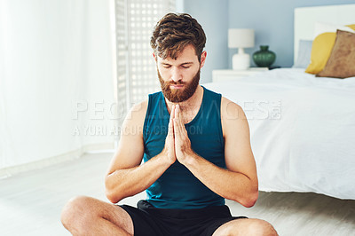 Buy stock photo Shot of a handsome young man practising yoga in his bedroom