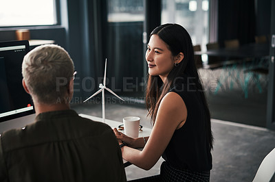 Buy stock photo Shot two attractive young businesswomen discussing ideas during a meeting with colleagues at work