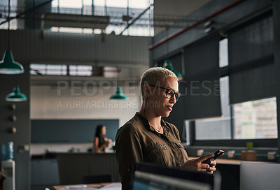 Buy stock photo Shot of an attractive young businesswoman using her cellphone at work
