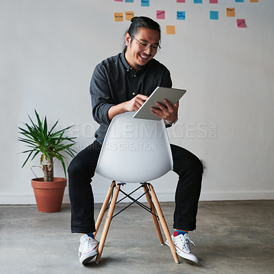 Buy stock photo Full length shot of a handsome young businessman sitting on a chair and using his digital tablet at work