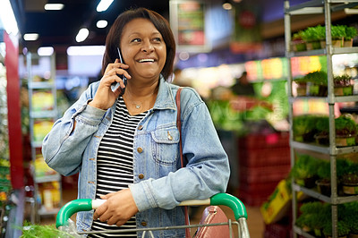 Buy stock photo Cropped shot of a mature woman talking on her cellphone while out shopping in a grocery store