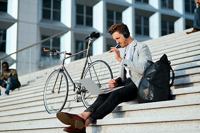 Buy stock photo Shot of a young businessman using a laptop and credit card on the steps in a city