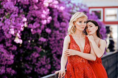 Buy stock photo Shot of two beautiful young women dressed in elegant wear standing on a balcony