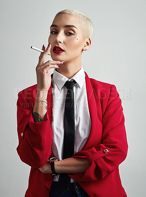 Buy stock photo Portrait of an attractive young and stylish businesswoman smoking a cigarette against a grey background