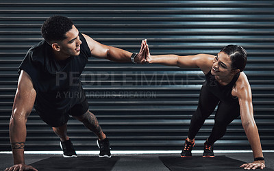 Buy stock photo Shot of two sporty young people giving each other a high five while doing pushup exercises together