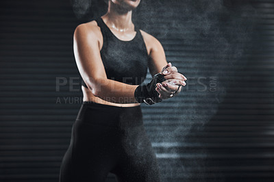 Buy stock photo Closeup shot of a sporty young woman rubbing chalk powder on her hands against a dark background