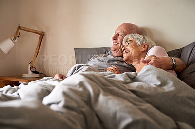 Buy stock photo Shot of a happy senior couple embracing and spending time together in their bedroom at home