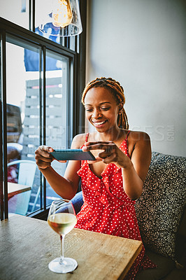 Buy stock photo Shot of an attractive young woman taking a picture of a glass of wine at a cafe