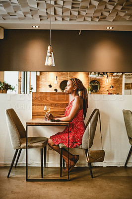 Buy stock photo Full length shot of an attractive young woman enjoying a glass of wine at a cafe