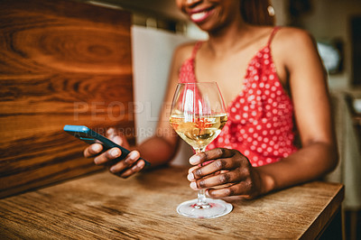 Buy stock photo Shot of an unrecognizable woman using her cellphone while enjoying a glass of wine inside a cafe