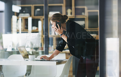 Buy stock photo Cropped shot of an attractive young businesswoman talking on her cellphone and typing on her laptop in the office