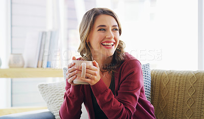 Buy stock photo Cropped shot of an attractive young woman sitting on her living room couch and holding a cup of coffee