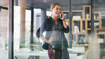 Buy stock photo Cropped shot of an attractive young businesswoman standing alone in her office and talking on her cellphone