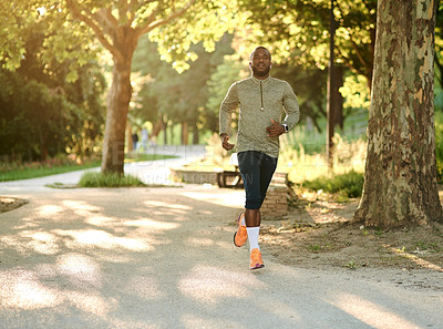 Buy stock photo Shot of a sporty young man out for a run at the park