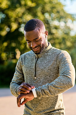 Buy stock photo Shot of a sporty young man checking his wristwatch while out for a run