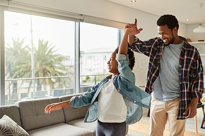 Buy stock photo Cropped shot of a cheerful little girl and her father having a dance together in the living room at home