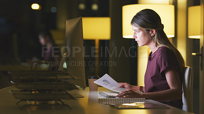 Buy stock photo Shot of an attractive young businesswoman going over some paperwork while working late in her office