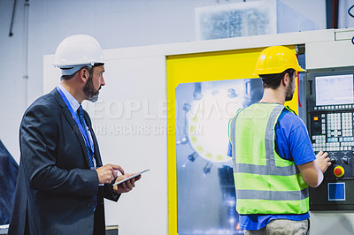 Buy stock photo Cropped shot of two confident engineers doing an inspection on machinery inside of a workshop