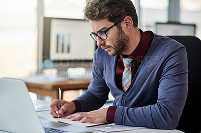 Buy stock photo Shot of a young businessman writing notes while working in an office