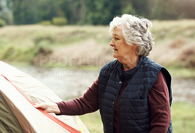 Buy stock photo Shot of a senior woman setting up a tent while camping in the wilderness