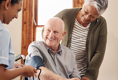 Buy stock photo Cropped shot of an attractive young female nurse strapping a blood pressure monitor around a elderly tenant in a wheelchair at an old age home