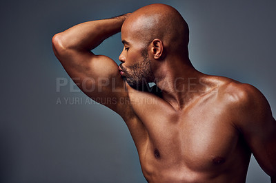 Buy stock photo Studio shot of a muscular young man kissing his bicep while posing shirtless against a grey background