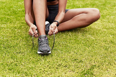 Buy stock photo Cropped shot of an unrecognizable young female athlete fastening her laces while working out at the track