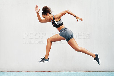 Buy stock photo Full length shot of an attractive young athlete jumping while on a track field during an outdoor workout session