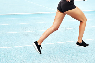 Buy stock photo Cropped shot of an unrecognizable athlete running along a track field alone during an outdoor workout session