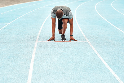 Buy stock photo Full length shot of an unrecognizable athlete crouching down and preparing to sprint along a track during a training session