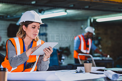 Buy stock photo Cropped shot of a focused female engineer working on blueprints while making use of a digital tablet inside of a workshop