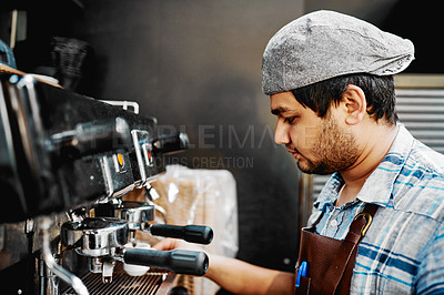 Buy stock photo Shot of a handsome young barista operating a coffee machine inside a cafe
