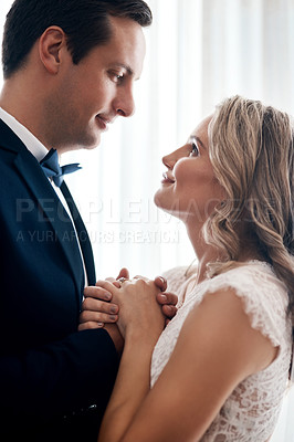 Buy stock photo Cropped shot of a happy young couple standing indoors and holding each other affectionately after their wedding