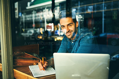 Buy stock photo Cropped portrait of a handsome young businessman sitting in a cafe alone and writing in a notebook