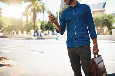 Buy stock photo Cropped shot of an unrecognizable man using his cellphone while out in the city