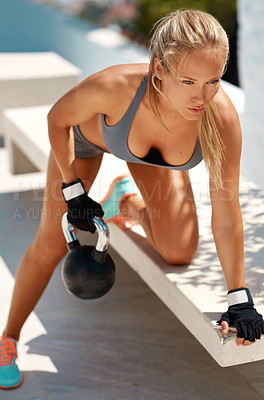Buy stock photo Full length shot of a beautiful young woman exercising with a kettle bell on a bench outdoors