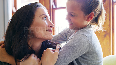 Buy stock photo Cropped shot of an affectionate young mother looking at her daughter while spending time with her at home