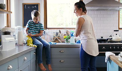 Buy stock photo Cropped shot of an affectionate young boy putting on rubber gloves while preparing to clean the kitchen with his mother at home