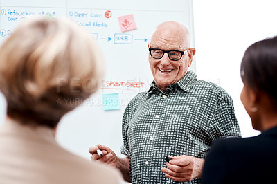 Buy stock photo Shot of a senior businessman giving a presentation to his colleagues in an office