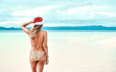 Buy stock photo Shot of a young woman wearing a christmas cap while standing on the beach