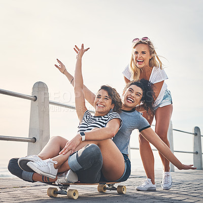 Buy stock photo Shot of a woman pushing her friends on a skateboard while out on the promenade