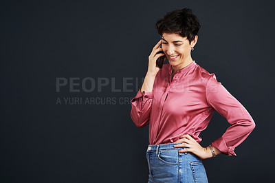 Buy stock photo Cropped shot of an attractive young businesswoman standing and talking on her cellphone against a black background in the studio