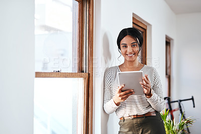 Buy stock photo Cropped portrait of an attractive young businesswoman standing and using a tablet in her office alone