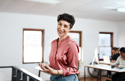 Buy stock photo Cropped portrait of an attractive young businesswoman holding a tablet while her colleagues work behind her in the office