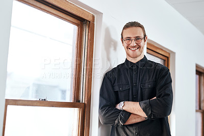 Buy stock photo Cropped portrait of a handsome young businessman standing alone with his arms crossed in his office