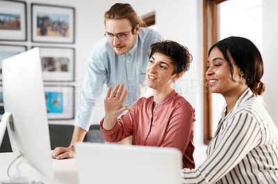 Buy stock photo Cropped shot of a diverse group of businesspeople working on a computer together during a meeting in the office