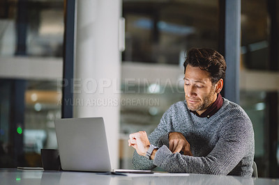 Buy stock photo Cropped shot of a handsome mature businessman sitting alone in his office and looking at his watch late at night
